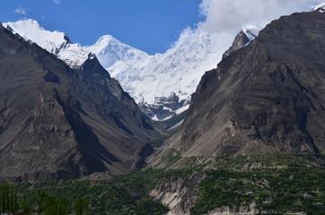 パキスタンのフンザ カリマバード中心部から見た絶景 美しい山々と新緑 青空と雲 名峰ディラン