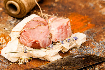 Raw fresh lamb meat and cleaver on dark background