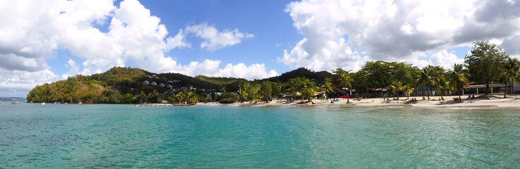 Superb panoramic view from the sea of the beautiful beach of Anse à l'Ane near the village of Trois-Ilets in Martinique facing the city of Fort-de-France