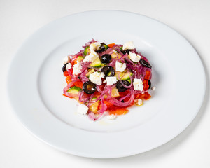 Fresh Greek salad in Plate with black olive,tomato,feta cheese, cucumber and onion isolated on white background.