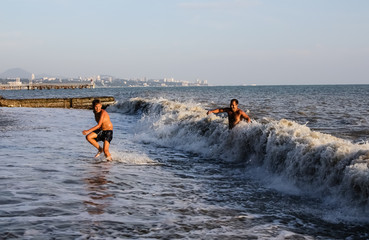 A man and a boy run out of the sea, a big wave