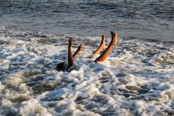 Teen boy under water, covered with a wave of arms and legs protruding