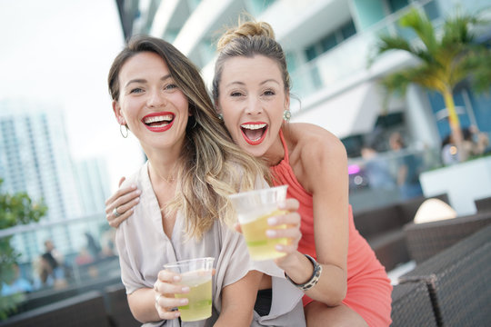 Two attractive funloving friends partying with drinks on rooftop bar in city