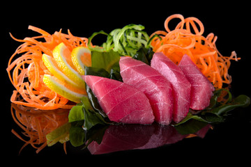 Delicious Tuna Sashimi (raw sliced fish) with carrot, cucumber, nori, lemon on black background. Traditional Japanese cuisine