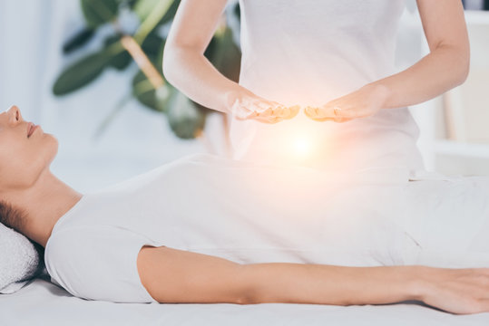 cropped shot of calm young woman receiving reiki treatment on stomach