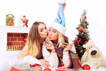 Happy blonde mom with her daughter by the fireplace with toys on Christmas Eve. portrait of two women by the fireplace in celebration on a white background in Christmas hats