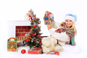 Happy woman in blue hat and white sweater on Christmas Eve near the Christmas tree with a fireplace, candy and toys