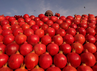 A vendor selling pomegranates looks on at a market in Srinagar