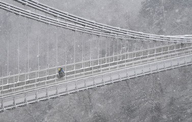A person cycles over the Clifton Suspension Bridge and Avon Gorge in Bristol during snowfall in southwest Britain