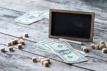 Tafel auf Holzbrett mit Dollar und Holzbuchstaben