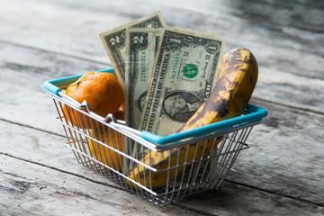 Obst mit Mängeln in Einkaufskorb mit Dollarscheinen