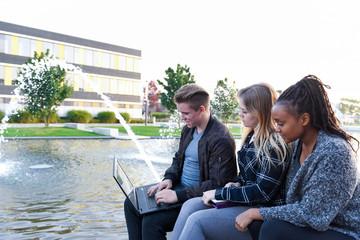 Gruppe Teenager arbeitet draußen mit Laptop