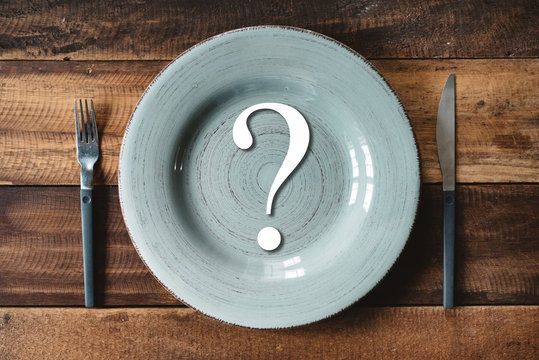 top view of a table set of cutlery with symbol of question mark in a plate. concept off diet and where or what to eat.