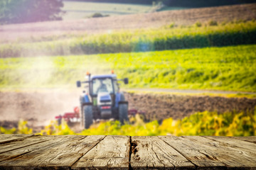 Table background of free space and spring rural landscape with tractor