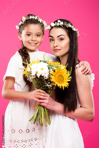 72526624c2 beautiful happy mother and daughter in white dresses holding flower bouquet  and smiling at camera isolated