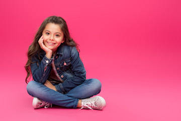 adorable happy child in denim clothes sitting with hand on chin and smiling at camera on pink