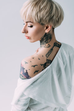 attractive woman with tattoos on back standing isolated on grey