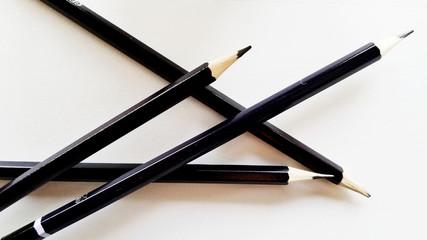 Black pencils on white table.