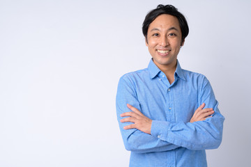 Portrait of happy Japanese businessman smiling with arms crossed