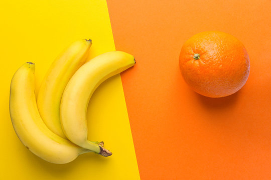 Bunch of yellow ripe bananas orange on duotone background. Creative trendy flat lay. Healthy food clean eating balanced diet superfoods concept. Copy space