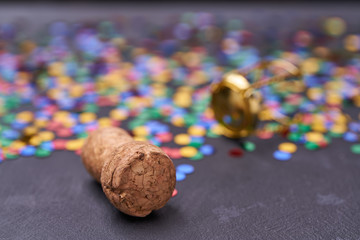Corks from champagne with confetti on a black background with  selective focus