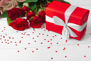 St. Valentines Day. Red roses and gift box on wooden table