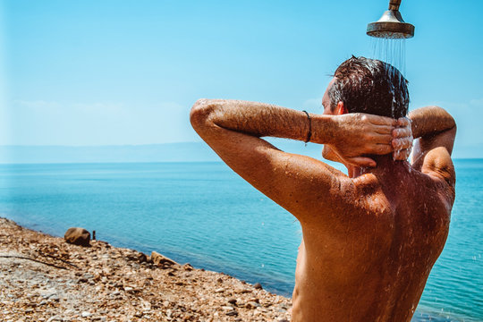 Men is having a fresh shower at the beach. Dead sea. Jordan
