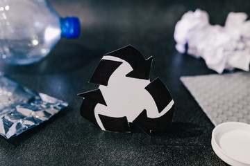 recycle symbol surrounded by reusable waste materials like plastic and paper