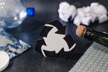 recycle symbol surrounded by reusable waste materials like plastic paper and glass