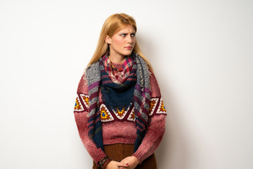 Hippie woman over white wall with confuse face expression while bites lip