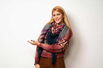 Hippie woman over white wall presenting an idea while looking smiling towards