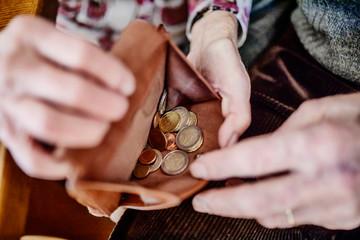 Senioren schauen in ihre fast leere Geldbörse