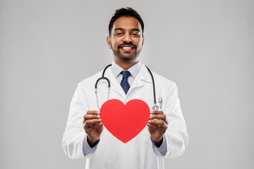 medicine, cardiology and healthcare concept - smiling indian male doctor or cardiologist in white coat with red heart shape and stethoscope over grey background