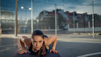 Beautiful Energetic Fitness Girl Doing Push Up Exercises. She is Doing a Workout in a Fenced Outdoor Basketball Court. Evening After Rain in a Residential Neighborhood Area.