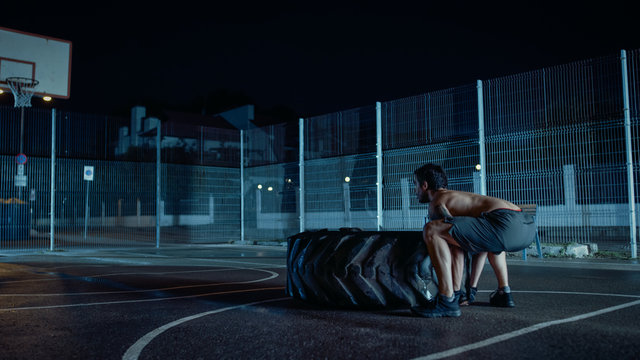 Strong Muscular Fit Young Shirtless Man is Doing Exercises in a Fenced Outdoor Basketball Court. He's Flipping a Big Heavy Tire in a Foggy Night After Rain in a Residential Neighborhood Area.