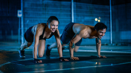 Smiling Happy Athletic Fitness Couple Doing Mountain Climber Exercises. Workout is Done in a Fenced Outdoor Basketball Court. Night After Rain in a Residential Neighborhood Area.