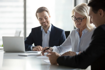 Smiling middle aged older businesswoman signing paper contract at group meeting, happy mature senior woman client puts signature on business document fills form making agreement deal, getting hired Wall mural