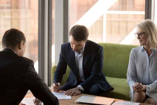 Two partners fill document form sign two-sided contracts for services at meeting, confident businessmen making sale purchase agreement deal put written signature on legal business papers
