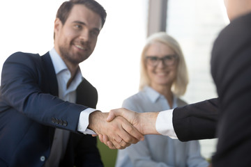 Smiling successful businessmen in suits shaking hands expressing respect, making investment deal at meeting, handshake as loyalty concept, welcoming new partner, collaboration, business reliability