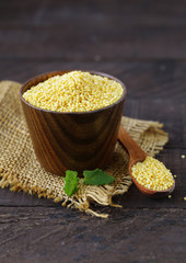 millet groats in a wooden cup, healthy food