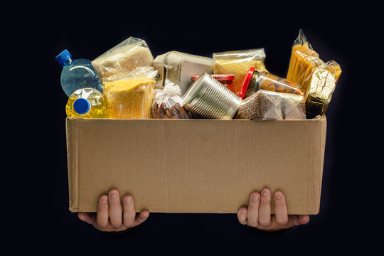 A man holding a donation box of different products on dark background