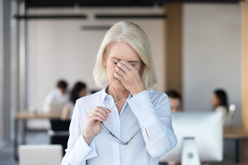 Tired fatigued senior female employee taking off glasses massaging nose bridge feeling eye strain, middle aged office worker suffering from bad blurry vision loss, eyestrain tension problem symptoms Wall mural