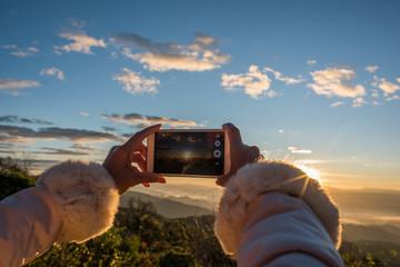 Hand holding a smartphone take a photo beautiful mountain