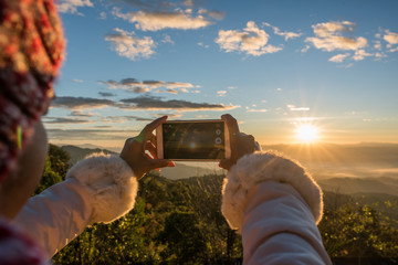 Hand holding a smartphone take a photo beautiful mountain