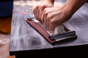 person prepares the surface for painting and sanding by hands an old wooden black table with a manual carpentry sandpapers holder