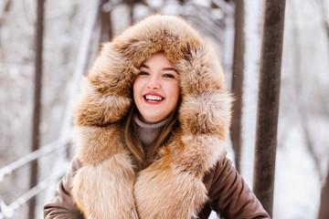 Beautiful girl in fur on a winter background posing on camera, enjoying life, laughing, beautiful smile with white teeth, emotion, joy, fashion