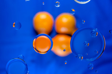 circles of tangerine color on a dark blue background with blue circles