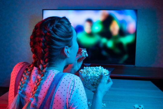 A young girl watching movies and eating popcorn with a bowl on the background of the TV. The color bright lighting, blue and red. Relax, rest at home when watching TV, film. Background for design