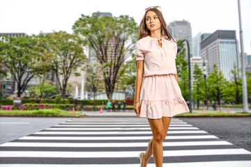 Slim young woman in pink dress on street in Japan. Spring time and free space for your decoration.