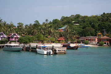 Ko Pha-ngan island riviera with boats near pier, palm trees and bungalow houses